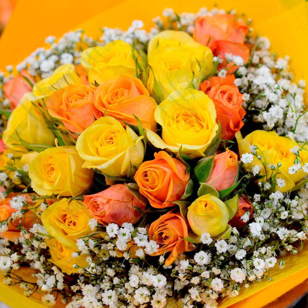 Букет из желтых и оранжевых роз с гипсофилой в упаковке